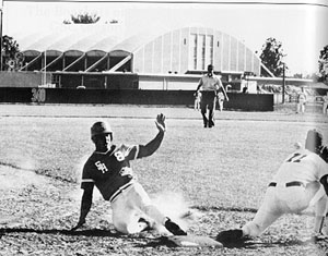 Baseball player sliding to plate.