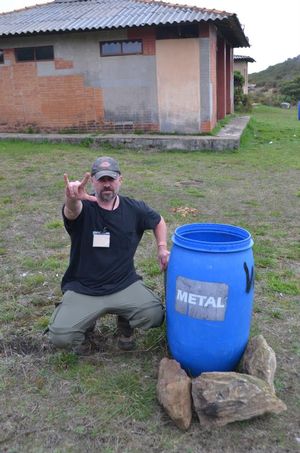 Dr. Randle next to a blue bucket labelled metal