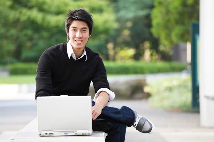 Young Asian Man sitting on a stone wall with  a laptop