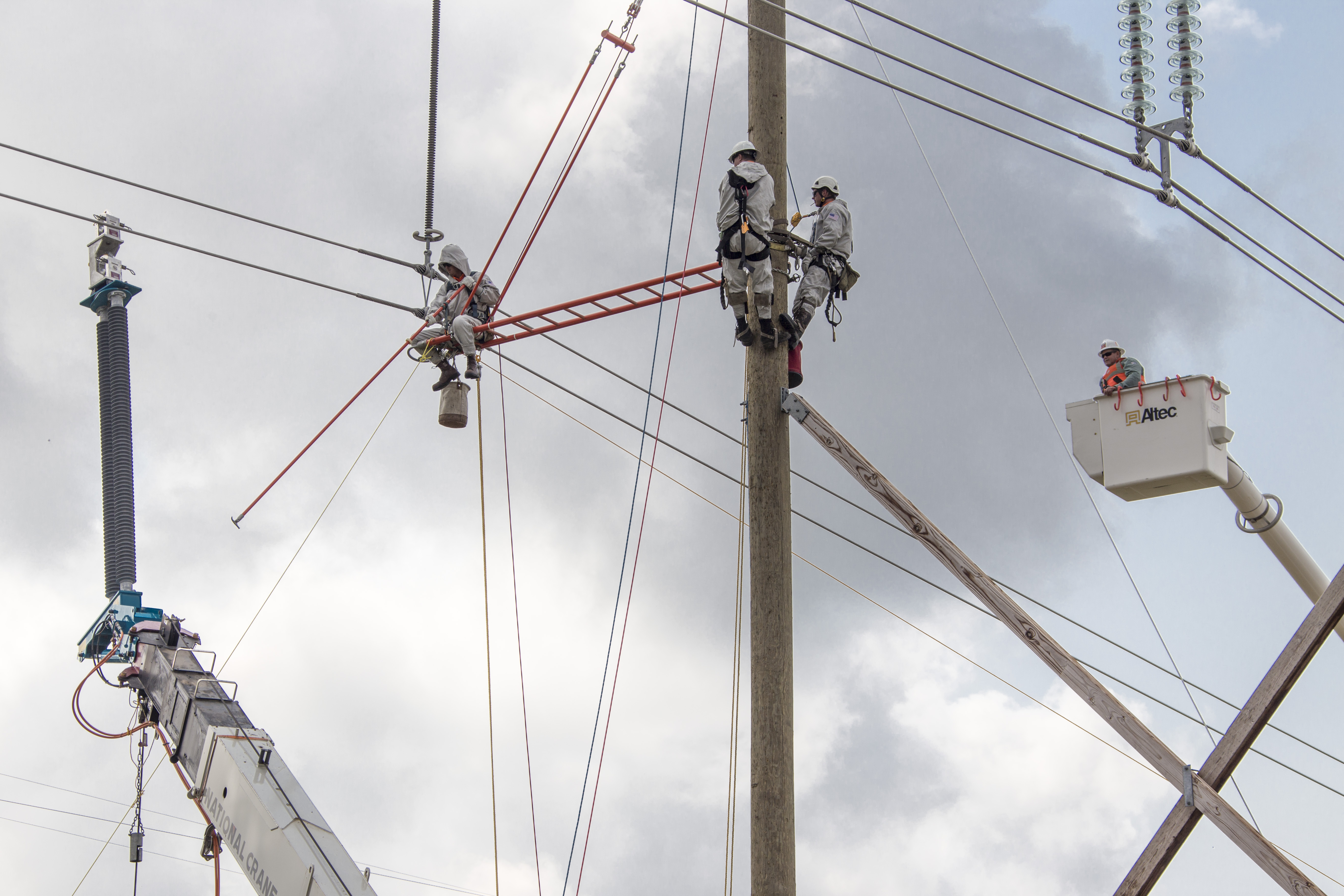 Engineers climbing power poles