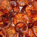 Bright orange mass of spiraled blown glass artwork by glass artist Jason Lawson