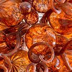 Bright orange mass of spiraled blown glass artwork by glass artist Jason Lawson
