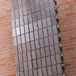 Tim Prentice's untitled kinetic sculpture of metal sheets affixed to the brick wall of the Performing Arts Center at SHSU