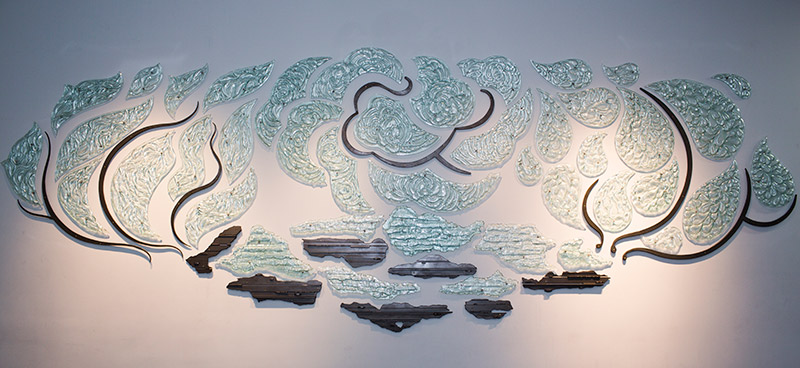 Artist Kathleen Ash's Elemental Mandala, glass shapes and metal affixed to the wall in a large, cloud-like pattern
