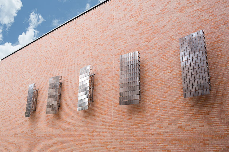 Numerous metal squares making up larger squares on the exterior wall of the PAC