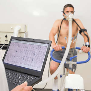 Person with breathing apparatus on exercise bike