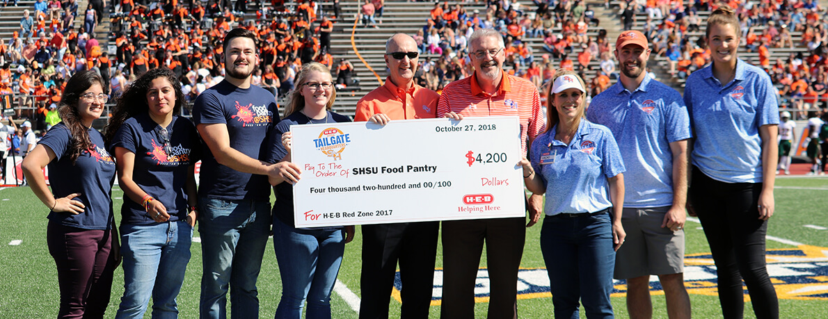 HEB presents check to food pantry at football game