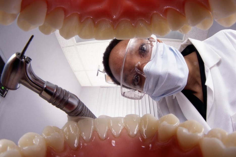Dentist looking at the teeth of a patient from inside patients mouth