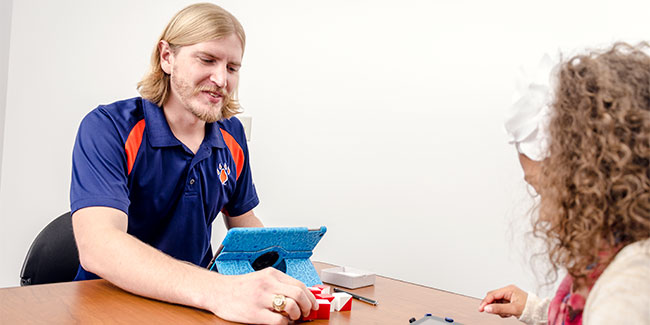 An SHSU psychologist works with a little girl by playing with blocks.