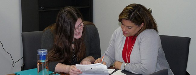 Two woman work together on a packet of papers.