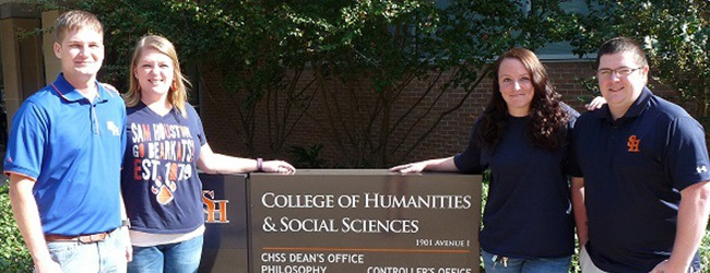 Four students stand by the sign for the College of Humanities and Social Sciences building.