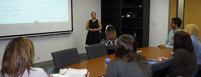 A woman gives a presentation in a conference room.