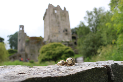 thumbnail view of Bearkat Pride - Brittney Boyd - Ireland - Summer 2019 - Rings at Blarney Castle - Male and Female rings displayed on a rock bench with Blarney castle in the background