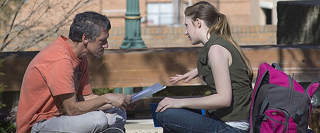 Guy Reading to Girl on Bench