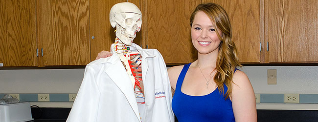 Danae Tidwell with arm around plastic skeleton wearing lab coat