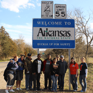 Photograph in front of Arkansas state sign for section named Spring Break Service