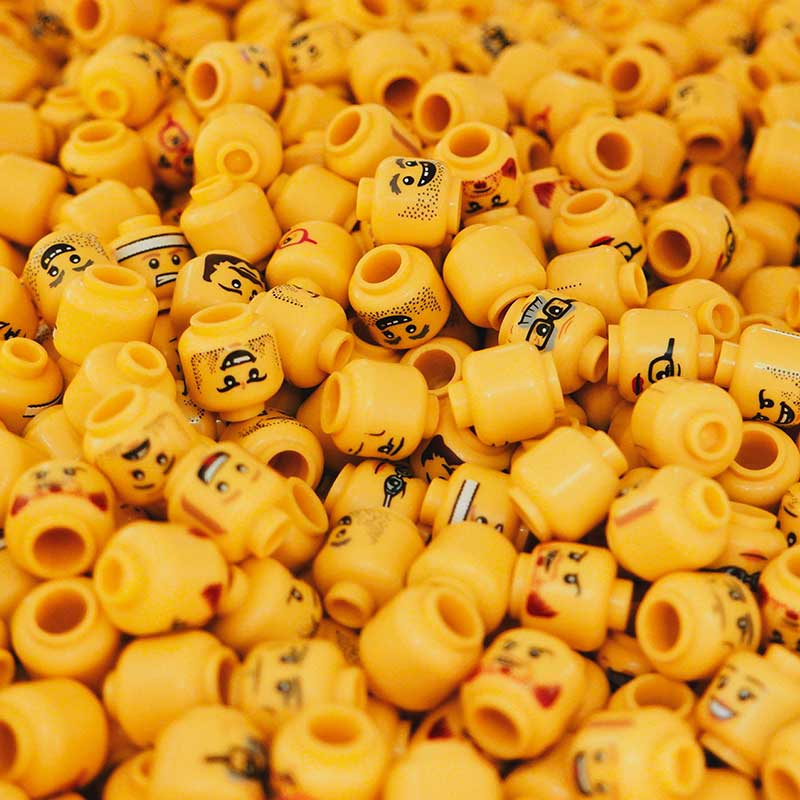 group of yellow lego heads with varying faces