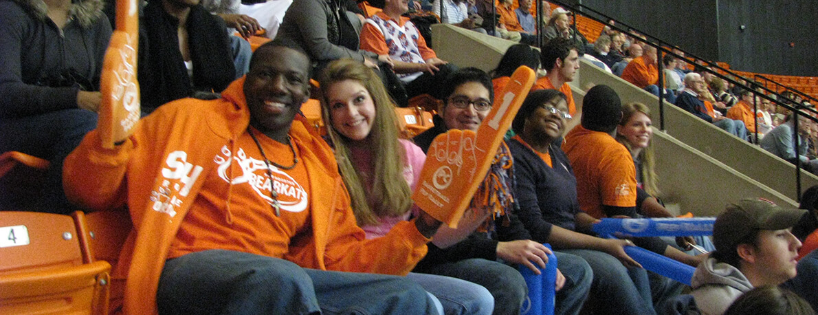 students sitting in stand smiling and holding up foam fingers