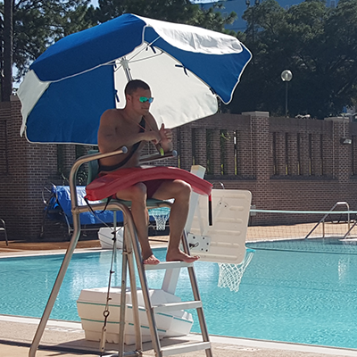 Lifeguard sitting in station watching over pool