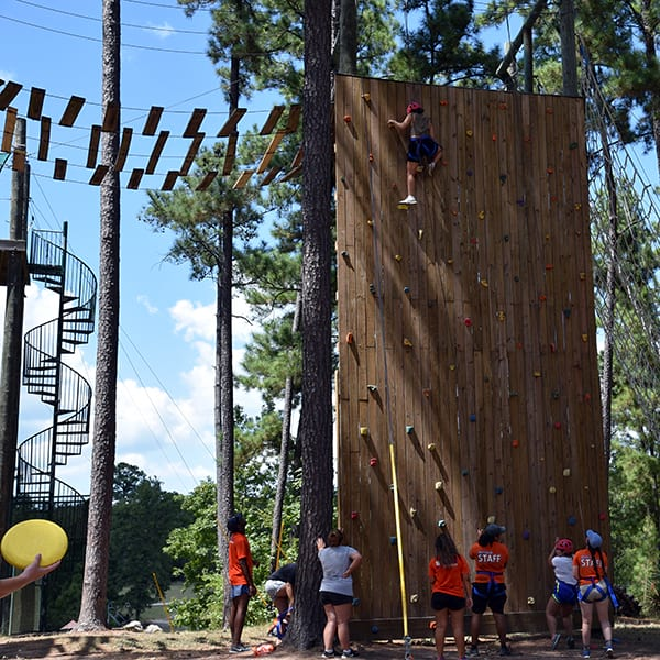 campers doing rock wall with challenge course