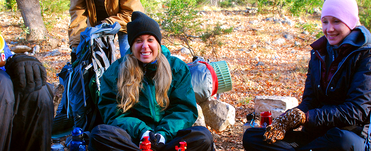 Hikers smiling and taking a rest bundled in warm clothing