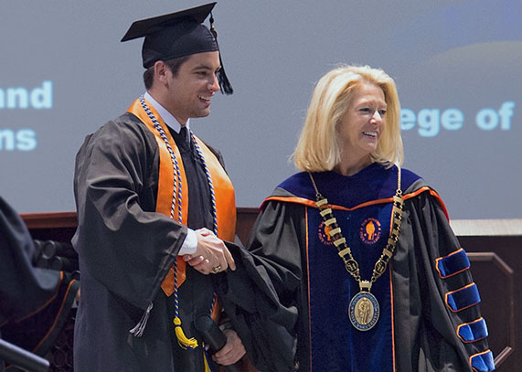 University President Dana Hoyt presenting a student with his degree on stage, during graduation.
