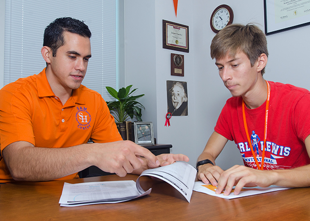 An advisor and student sit at a desk and review a degree plan.