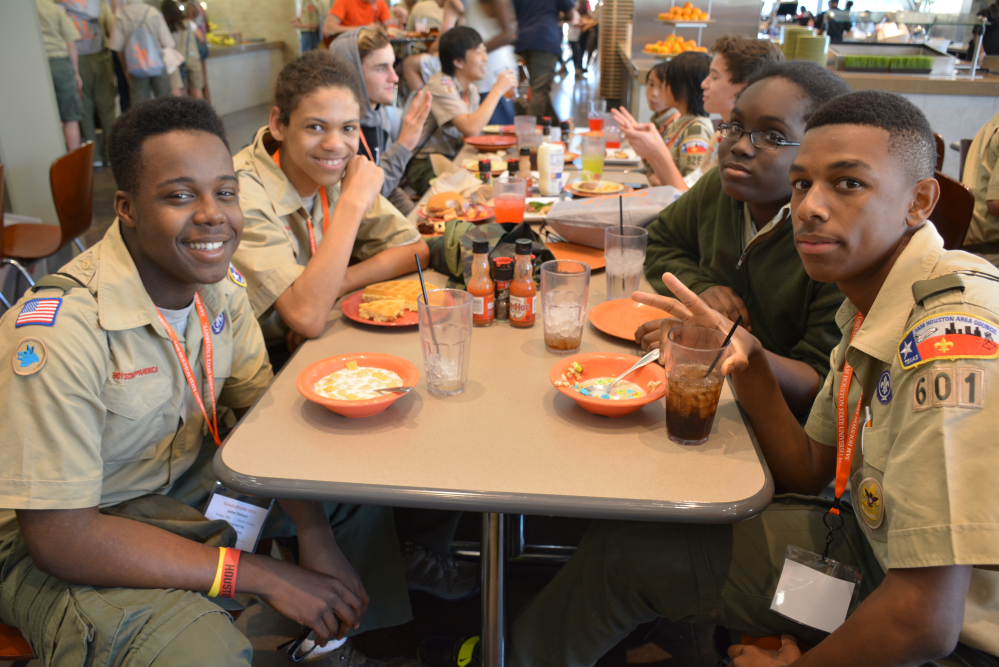 Boy Scouts smile at the camera as they eat lunch.