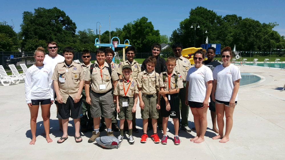Boy Scouts stand by the pool with their lifeguard instructors.