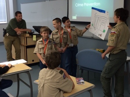 Boy Scouts giving a presentation on crime prevention with a posterboard.