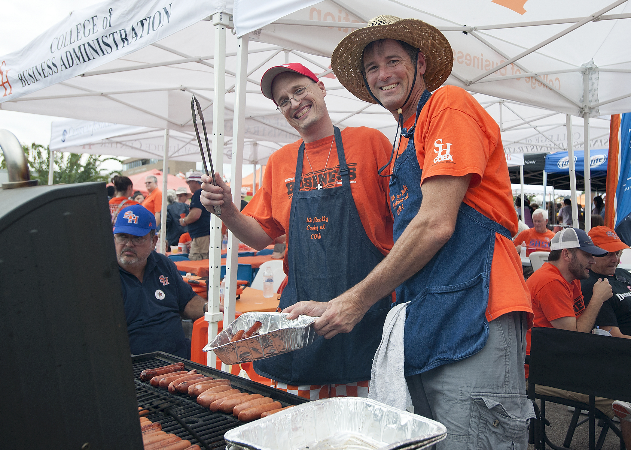 Two Bearkat fans grill some hotdogs, surrounded by a sea of orange and white tents and people.