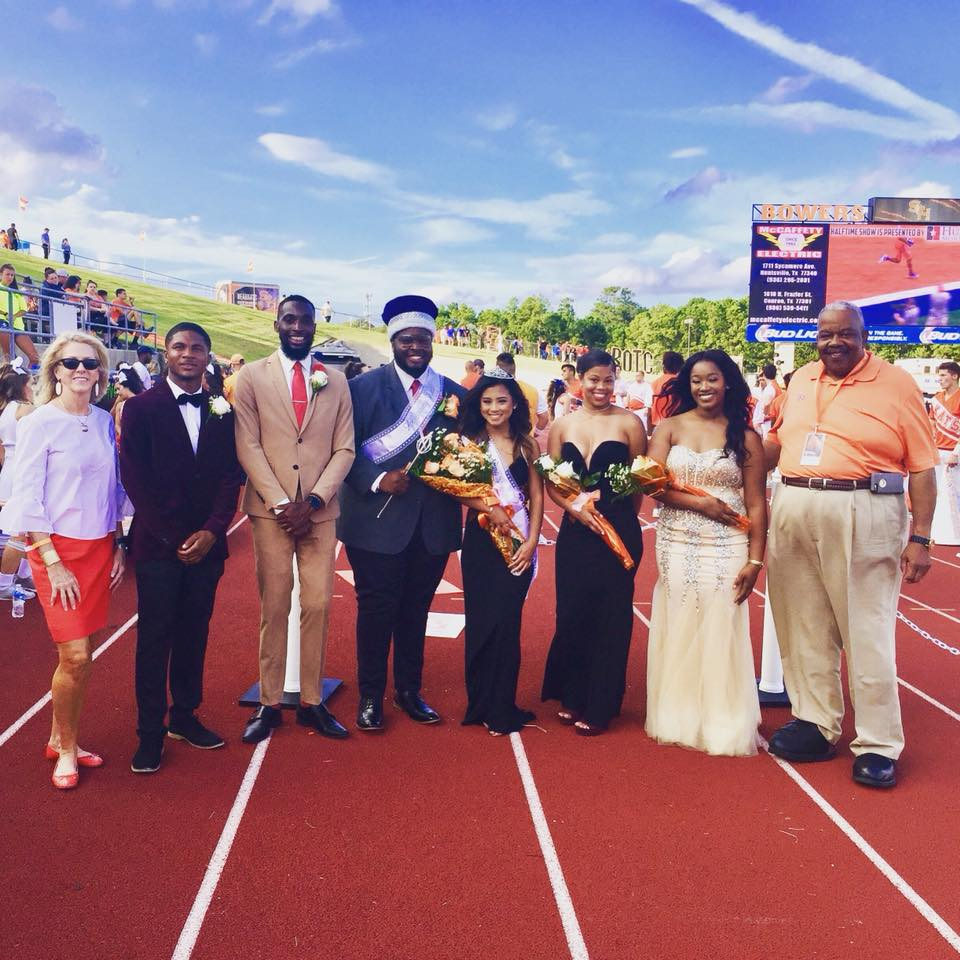 The homecoming court stands on the field with President Dana G. Hoyt and Mr. Frank Parker.