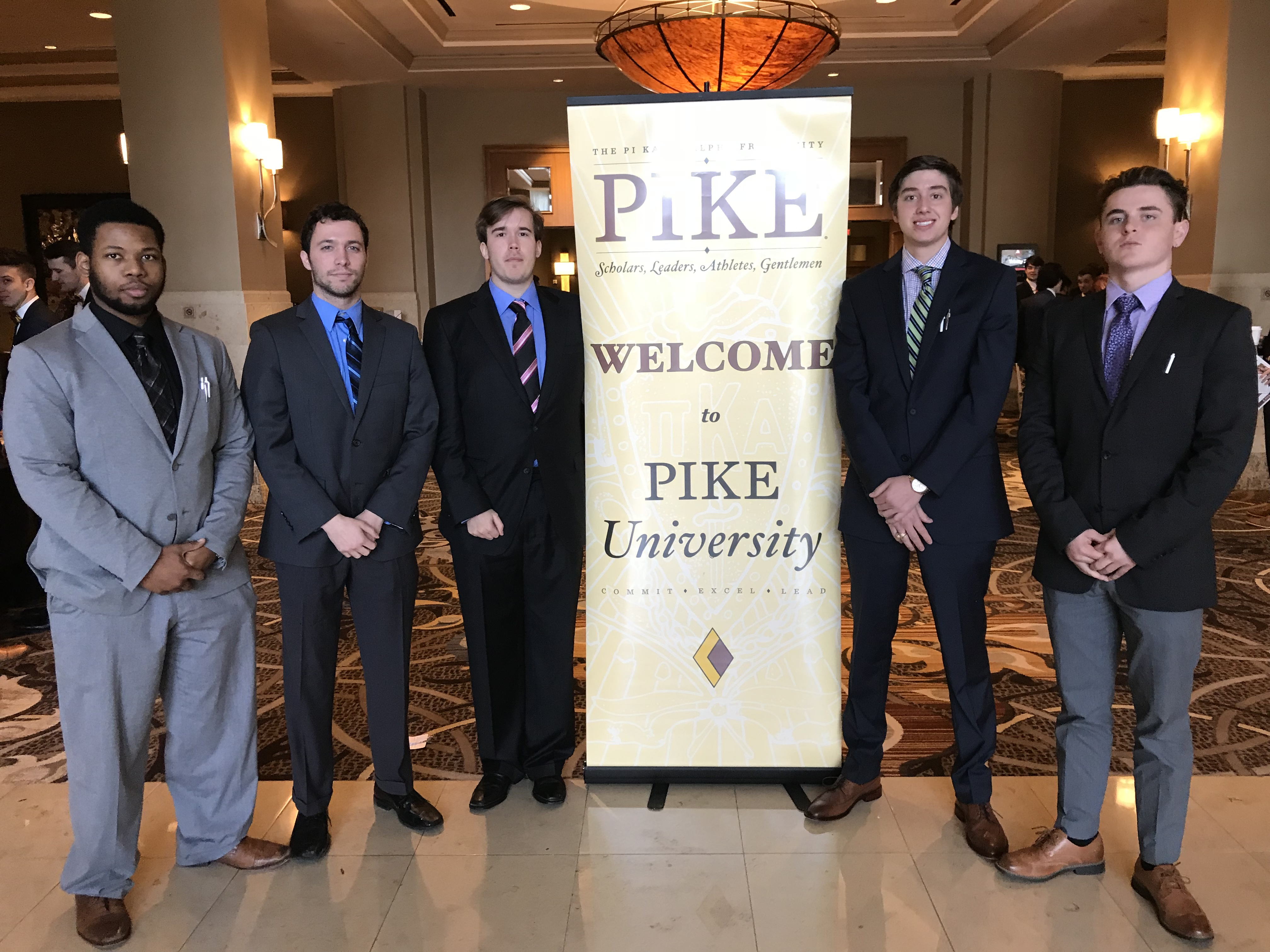 5 men in suites standing next to a sign that welcomes them to Pike University.