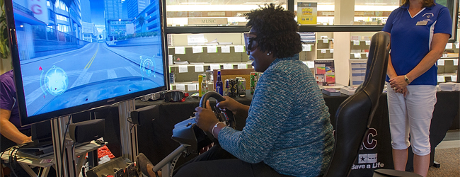 An individual playing a drunk driving simulator.