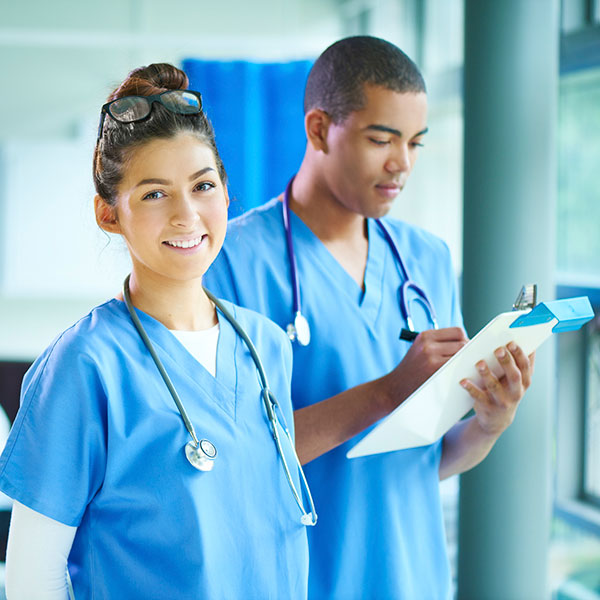 male nurse looking at clipboard and female nurse looking towards you