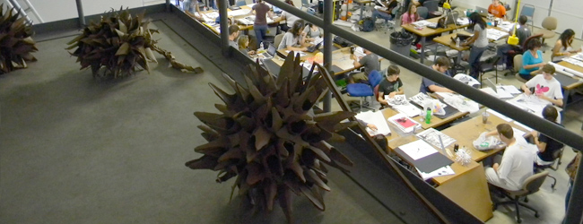 cardboard sculptures on 2nd floor of wash building with students working at stations below