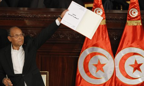 Tunisia's president, Moncef Marzouki, holds a copy of the new constitution after signing it before deputies in the national assembly on Monday. Photograph: Anis Mili/Reuters