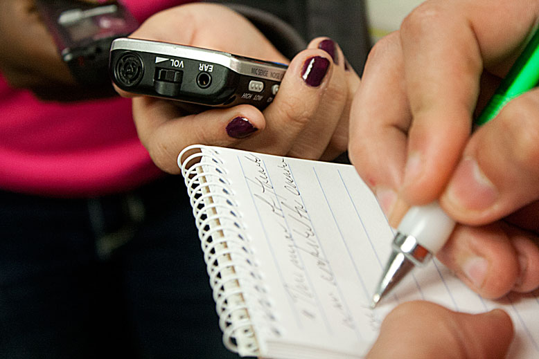 a person holding a small voice-recorder while another person takes notes on a notepad