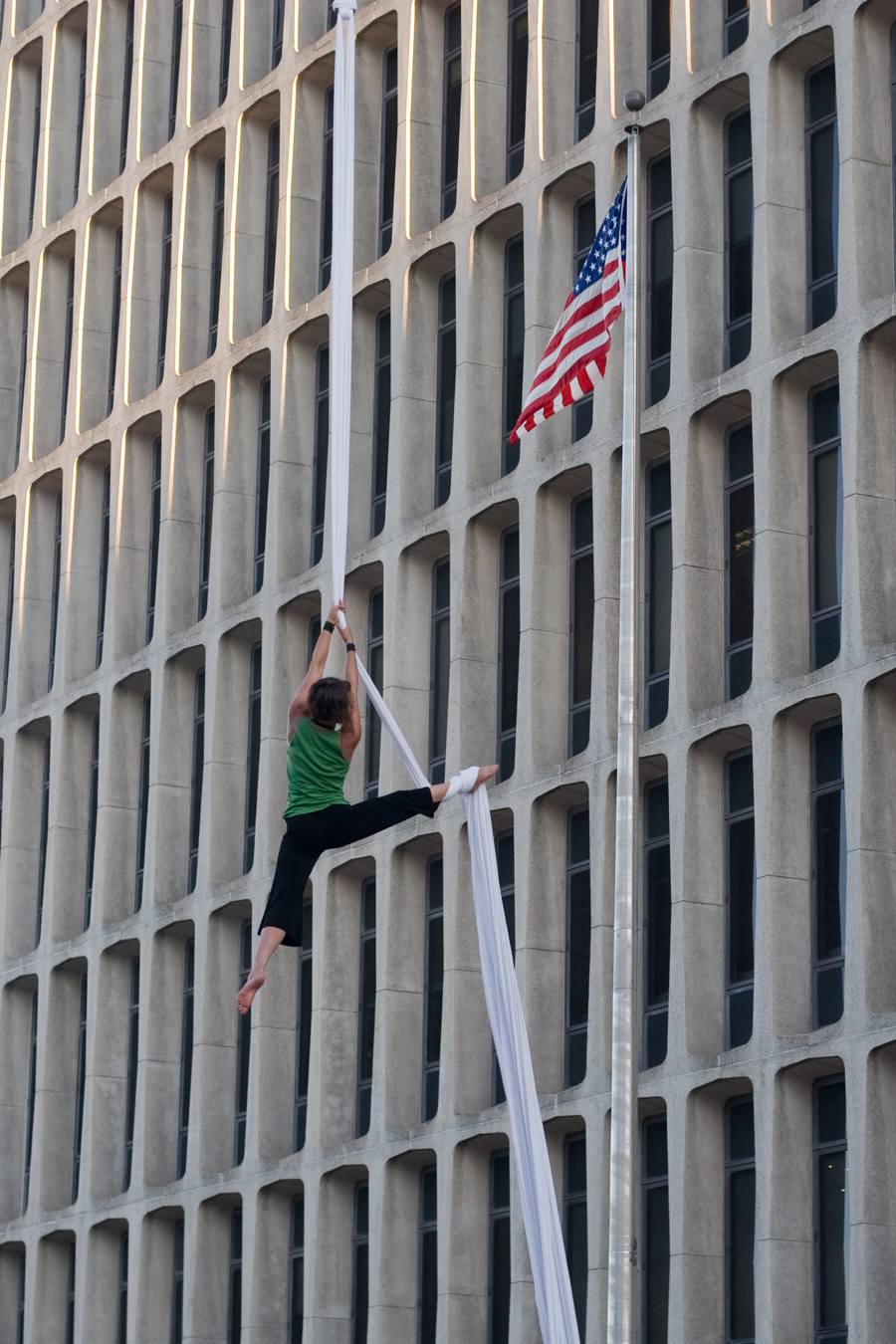 Alicia Carlin hanging on a cloth between buildings