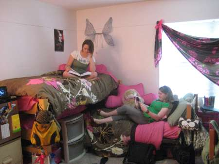 Dorm room with student on bed.