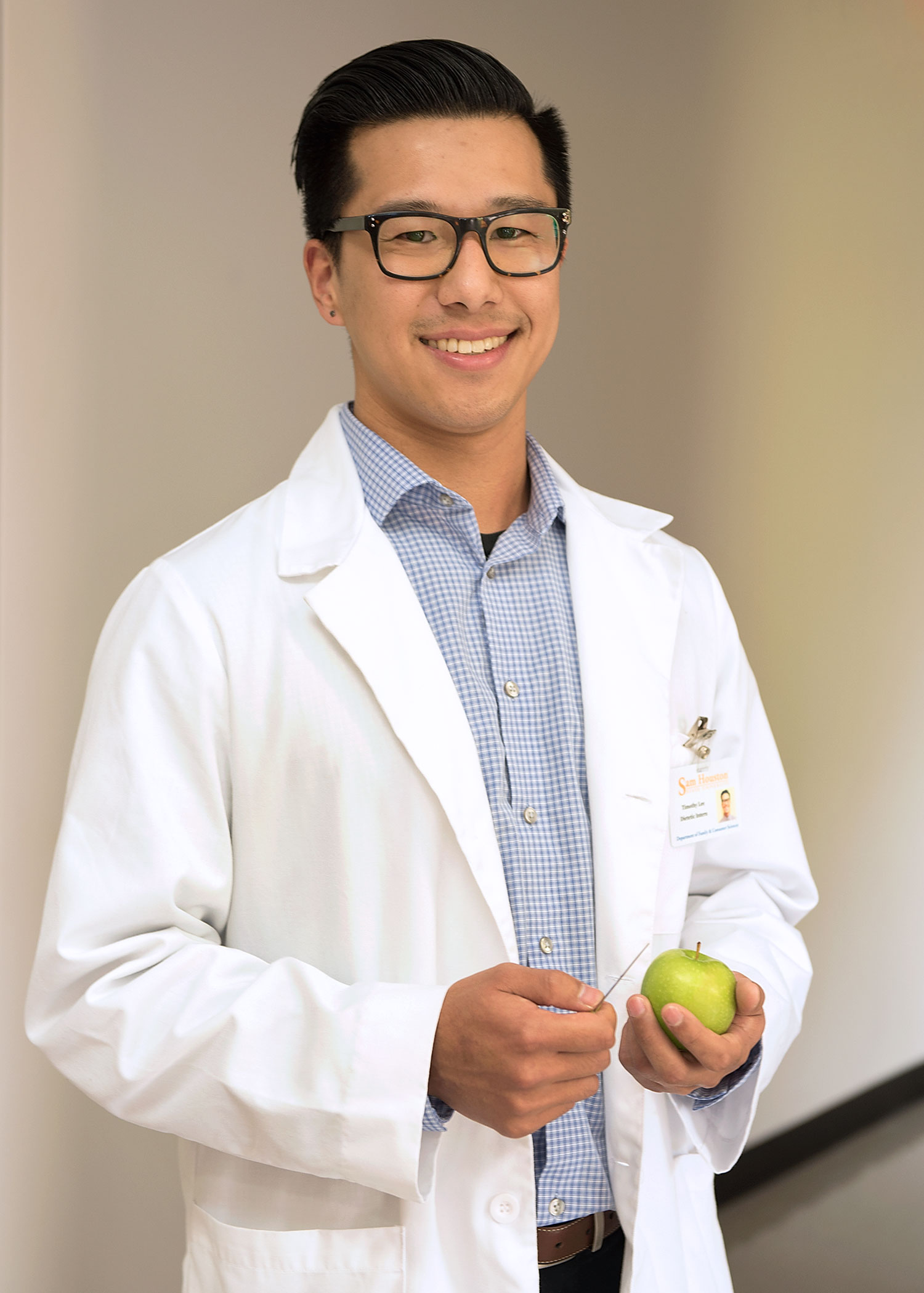 Student wearing a lab coat, holding a green apple