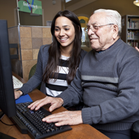 Older gentlemen at a computer while a young adult helps him