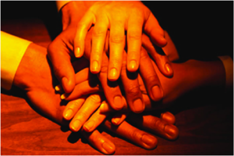 Hands on top of hands indicating togetherness