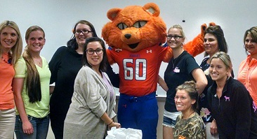 A group of students post for a picture with Sammy Bearkat.