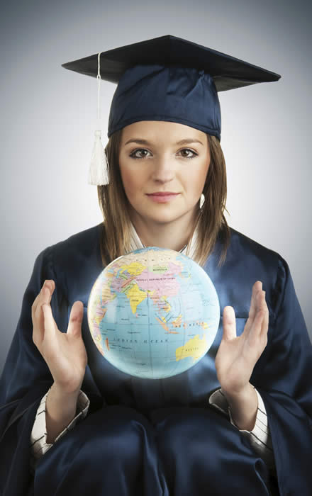 Young woman in graduation cap and gown with a floating globe