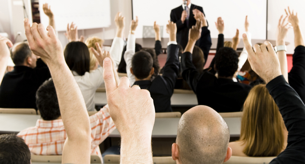 Classroom of professionals raising their hand