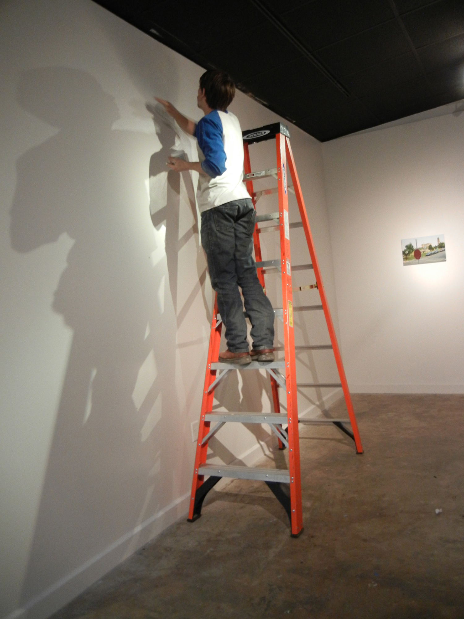 student gallery worker painting gallery wall