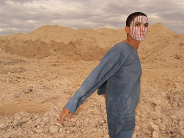 A man with a painted face stands in a desert setting.