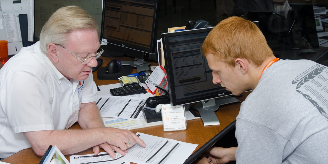 Man helping guy with paperwork at desk