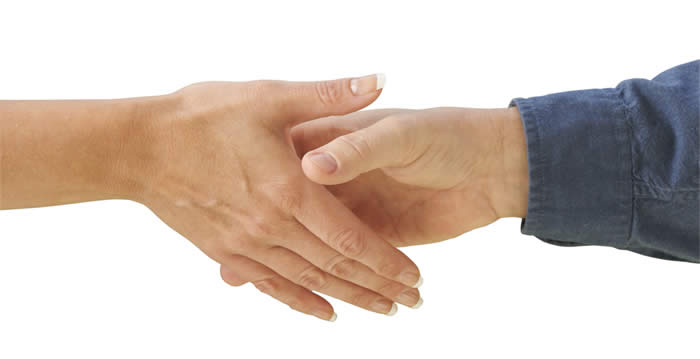 A male and a female hand reach out towards each other to shake hands.